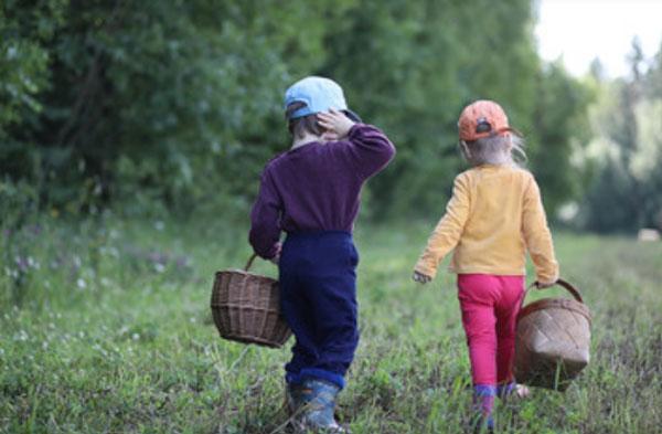 Мальчик с девочкой идут по лесу. У них в руках корзины. Дети в штанах и кофточках, с головными уборами