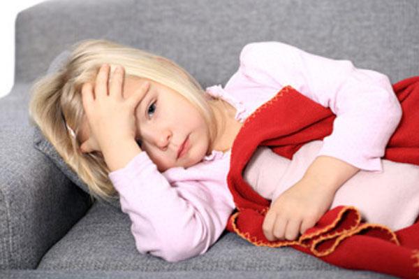 Девочка лежит на диване, держится за голову