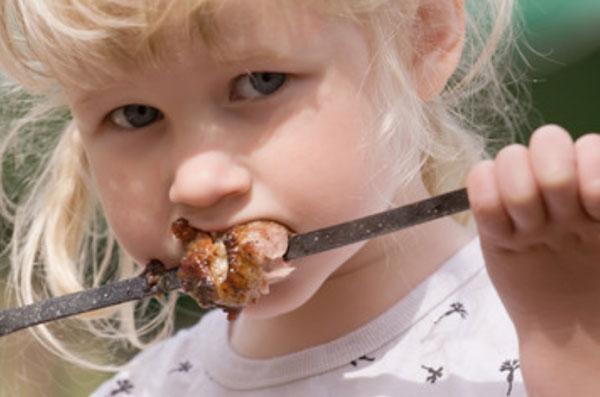 Маленькая девочка кусает мясо с шампура