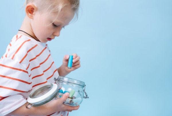 Ребенок достает батарейку из баночки