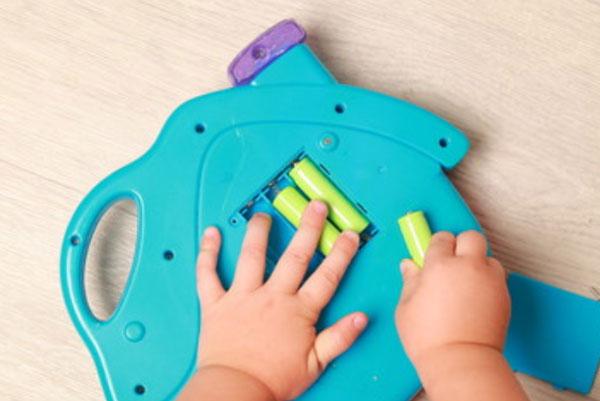 Ребенок достает батарейки из игрушки