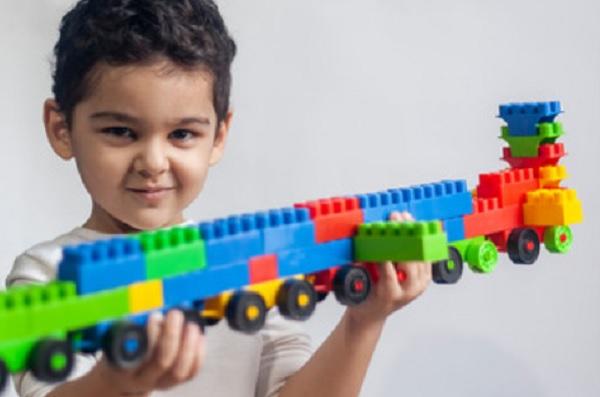Ребенок держит поезд, построенный из конструктора