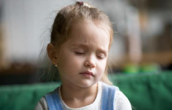 Девочка сидит с закрытыми глазами