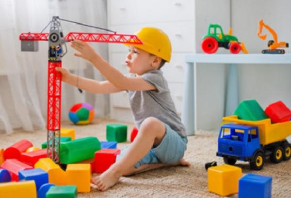 Ребенок играет с краном. Рядом разбросанные кубики