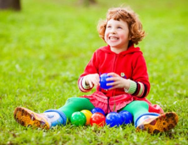 Девочка сидит на траве. Возле нее лежат маленькие мячики