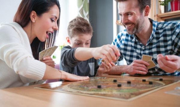 Ребенок играет с родителями в настольную игру