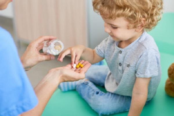 Ребенок берет витаминки