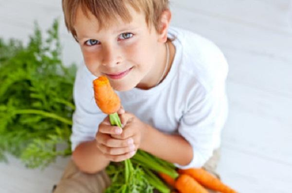 Мальчик грызет морковку