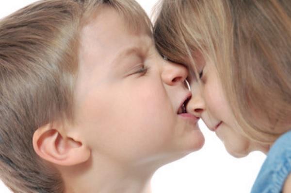 Мальчик пытается укусить девочку за носик