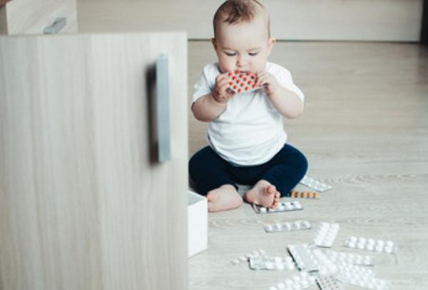 Возле ребенка на полу много таблеток. Он одну пластинку с лекарствами засовывает в рот