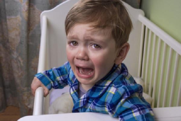 Ребенок стоит в кроватке и сильно плачет