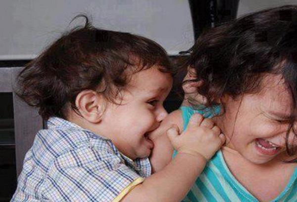 Мальчик кусает девочку за плечо