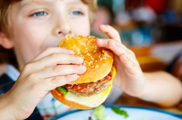 Мальчик ест бургер
