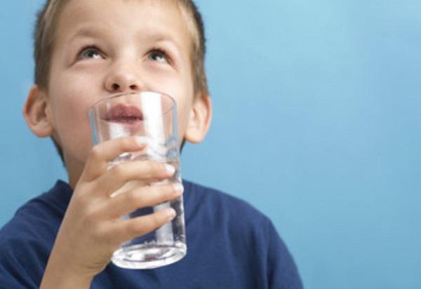 Ребенок пьет воду со стакана