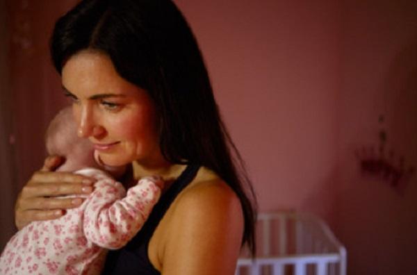 Мама держит ребенка на руках в темной комнате