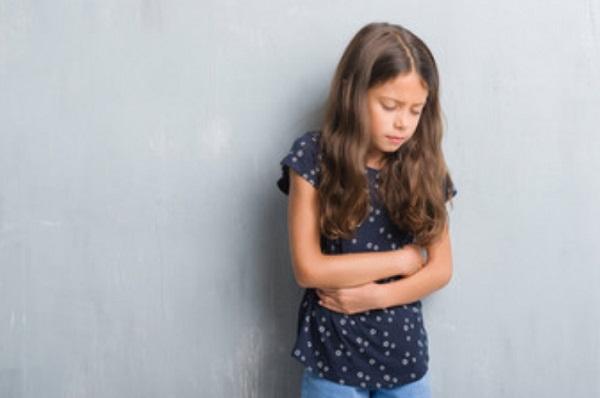 Грустная девочка стоит возле стены и держится за живот