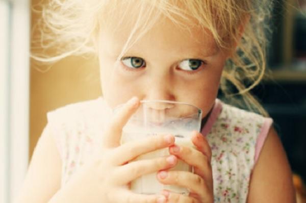 Девочка пьет молоко со стакана