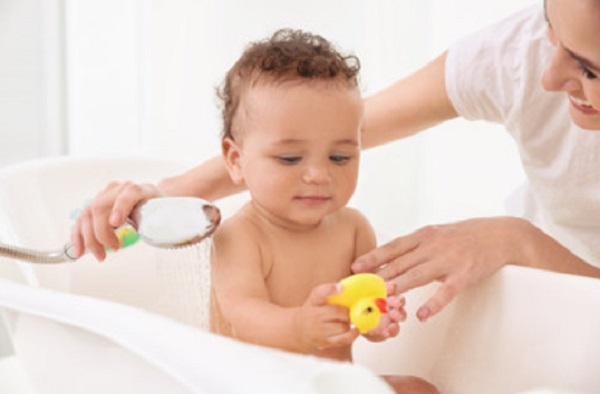 Ребенок играет резиновой уточкой при приеме ванны