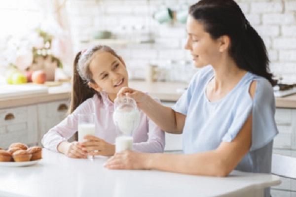Мама наливает молоко дочери и себе