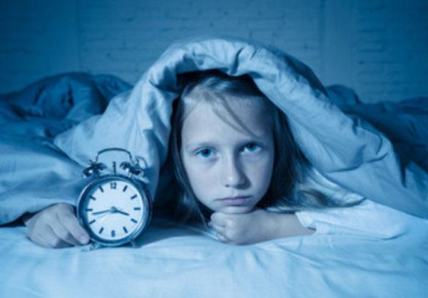 Девочка выглядывает из-под одеяла с будильником в рук