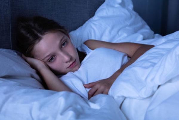 Замученная девочка лежит в постели в темной комнате