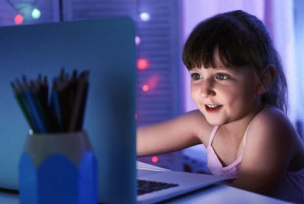 Девочка сидит возле ноутбука
