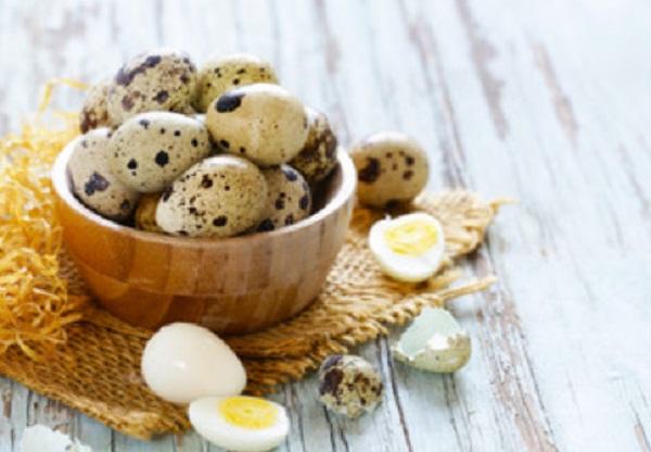 Мисочка с варенными перепелиными яйцами. Рядом лежат очищенные и разрезанные яички
