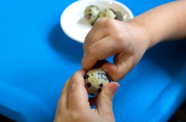 Ребенок чистит варенное перепелиное яйцо