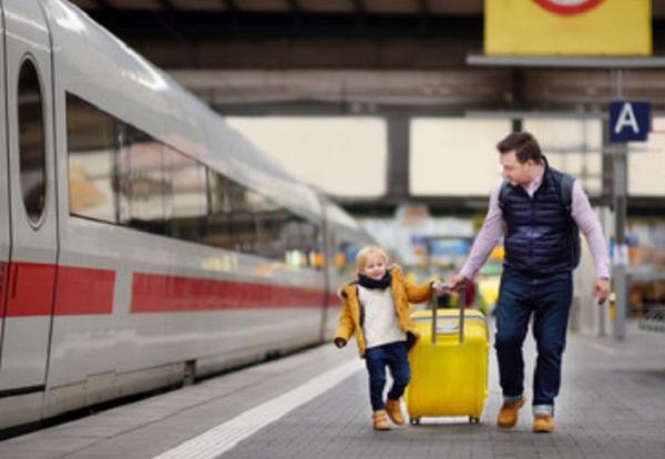Ребенок с папой тянут чемодан на платформе возле поезда