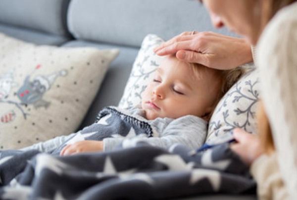Ребенок в постели, мама трогает его лобик