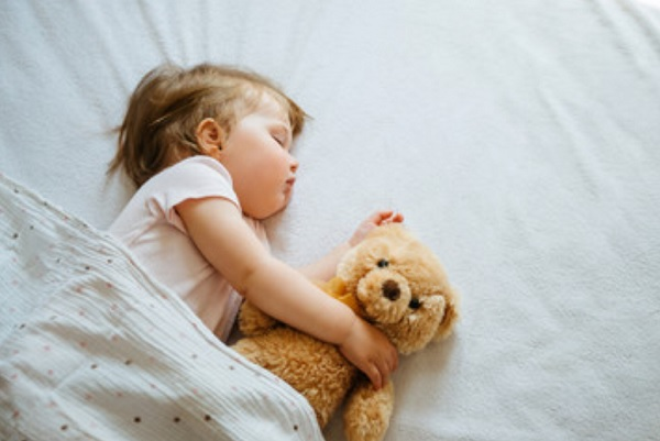 Ребенок спит в обнимку с мишкой