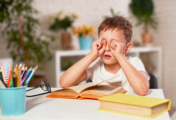 Ребенок трет глаза. На столе лежит книга