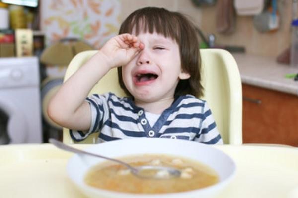 Ребенок плачет. Перед ним стоит тарелка с едой