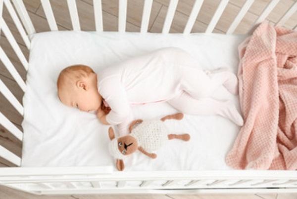 Грудной ребенок лежит в кроватке