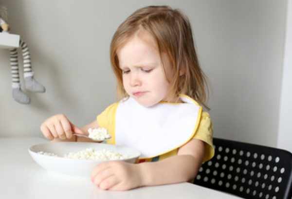 Девочка набрала в ложку еду, но с недовольством на нее смотрит