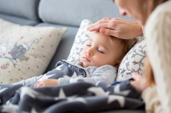 Ребенок в постели. Мама трогает его лобик