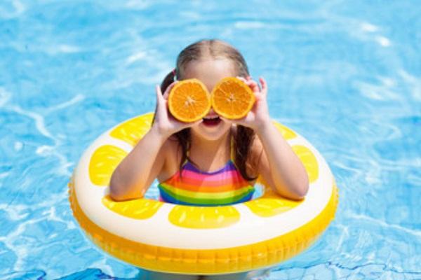 Девочка держит перед глазами кружочки апельсина