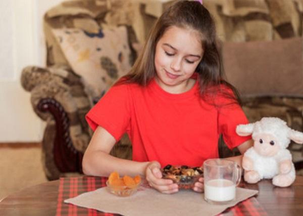 Девочка смотрит на тарелку с сухофруктами