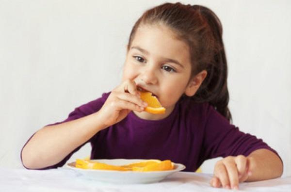 Девочка ест нарезанный апельсин