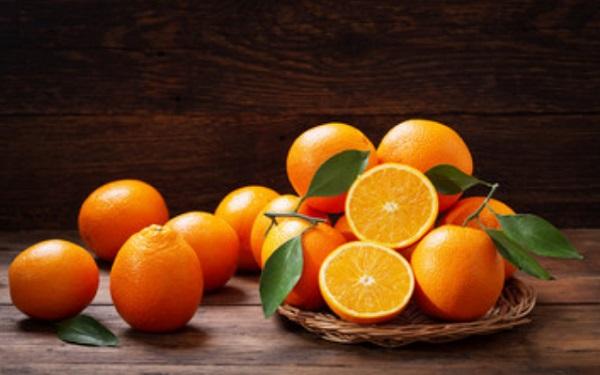 Апельсины на тарелке и на столе