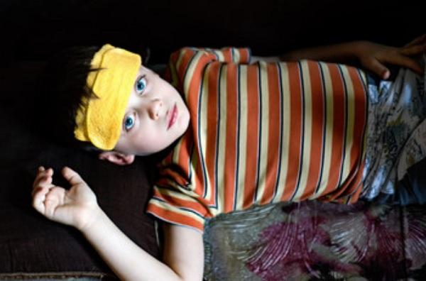 Ребенок лежит с тряпочкой на лбу