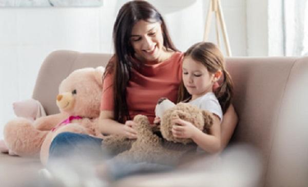 Мама с дочкой сидят на диване. У девочки в руках мягкая игрушка
