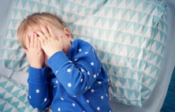 Ребенок лежит в кроватке, прикрывая лицо руками
