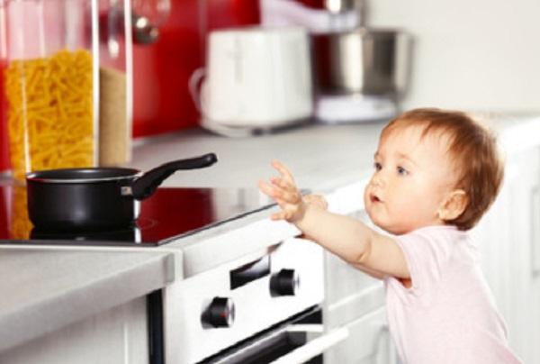 Ребенок тянется к сковороде, которая стоит на плите