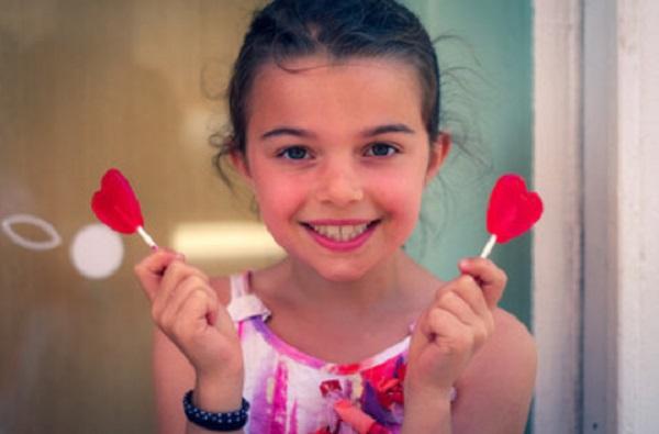Девочка держит в руках два леденца на палочках