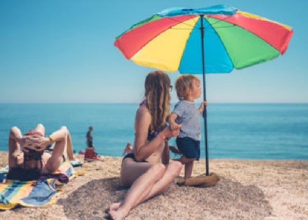 Ребенок с мамой под зонтиком на пляже