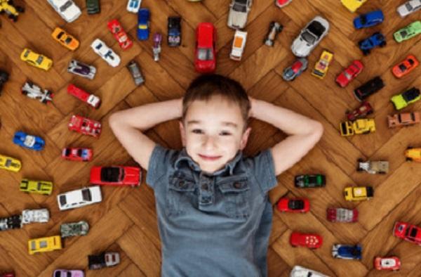 Мальчик лежит на полу, вокруг него множество машинок
