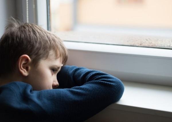 Уставший ребенок смотрит в окно
