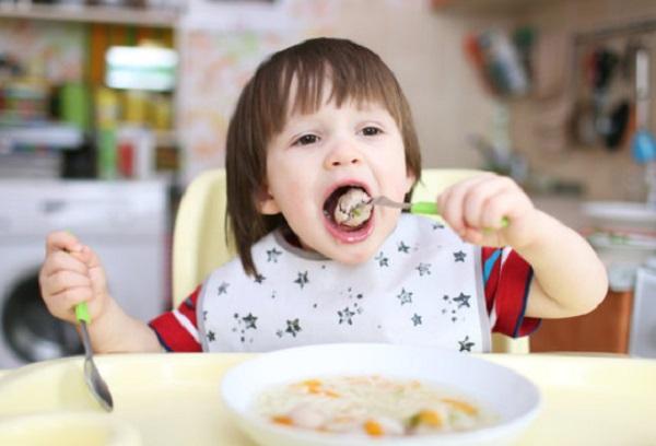 Ребенок ест мясную фрикадельку