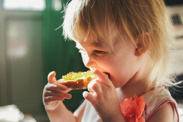 Девочка кусает бутерброд с красной икрой